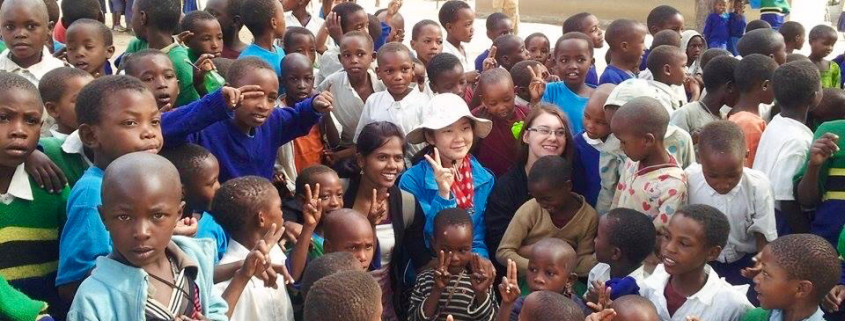 Missionaries surrounded by a crowd of Tanzanian children
